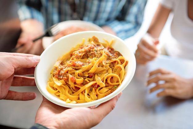 Pâtes alimentaires de rue dans une assiette en carton à emporter étant servi au client Photo Premium