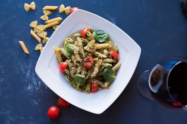 Pâtes au pesto, basilic frais et noix sur une plaque blanche sur fond bleu foncé Photo Premium