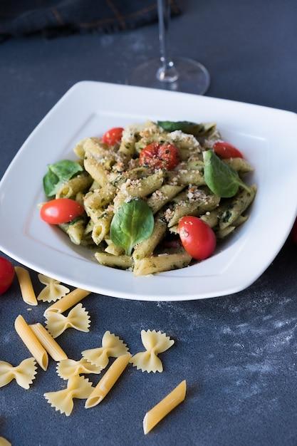 Pâtes au pesto, basilic frais et noix sur une plaque blanche. spaghetti sur fond bleu foncé Photo Premium
