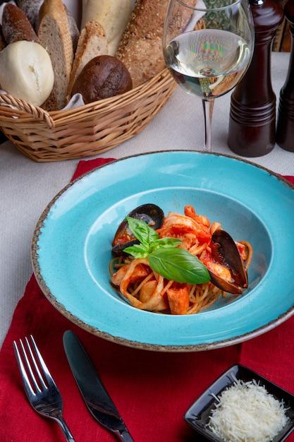 Pâtes aux fruits de mer et tomates sur fond clair Photo Premium