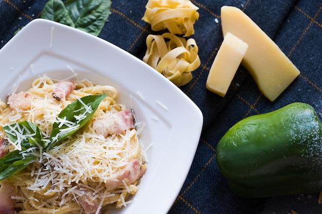 Pâtes Aux Lardons, Crème, Basilic, Parmesan, Ail, œuf (jaune) Sur Plaque Blanche Photo Premium