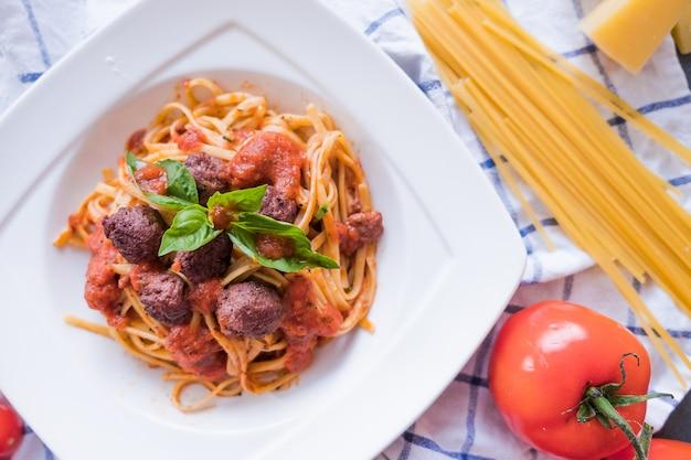 Pâtes bolognaises sur assiette blanche. spaghetti sur fond bleu Photo Premium