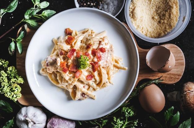 Pâtes Carbonara Dans Un Plat Blanc, Entourer L'ingrédient Frais Photo Premium