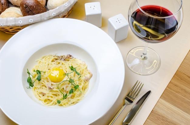 Pâtes carbonara sur plaque blanche au parmesan et jaune sur fond blanc Photo Premium