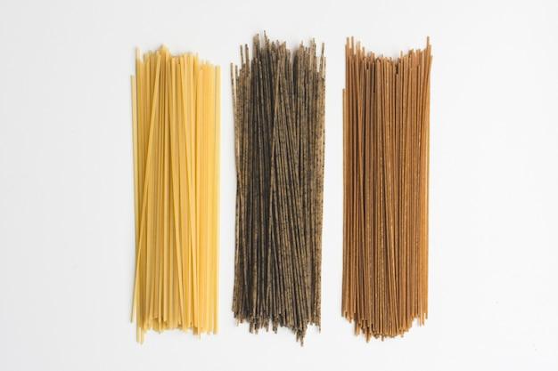 Pâtes entières spaghetti tricolora sur fond blanc Photo gratuit