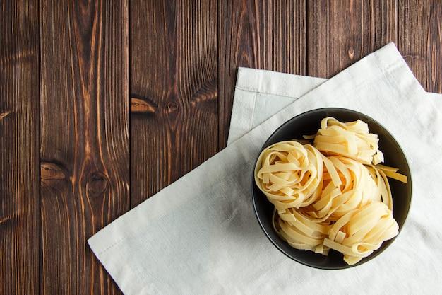 Pâtes Fettuccine Dans Un Bol Sur Fond De Serviette En Bois Et Cuisine. Mise à Plat. Photo gratuit