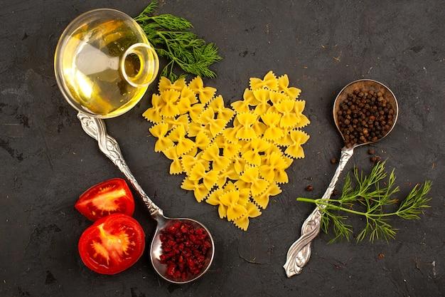 Pâtes En Forme De Cœur Jaune Cru Avec Des Tomates Rouges Tranchées, Des Herbes Vertes, De L'huile D'olive Et Des épices Brunes Sur Le Sol Sombre Photo gratuit