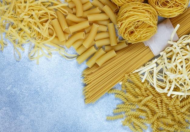Pâtes fraîches crues à partir de farine de grains entiers. spaghetti, nouilles aux oeufs, tortiglioni, fusilli et nids Photo Premium