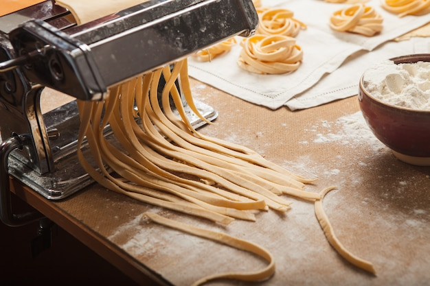 Les Pâtes Fraîches Et La Machine Sur La Table De La Cuisine Photo gratuit