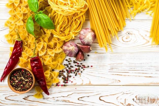 Pâtes Frisées Au Poivre Et Au Basilic Et Assaisonnement Sur La Table, Différentes Variétés De Pâtes, Fettuccine, Bucatini, Spaghetti Avec Trous Photo Premium