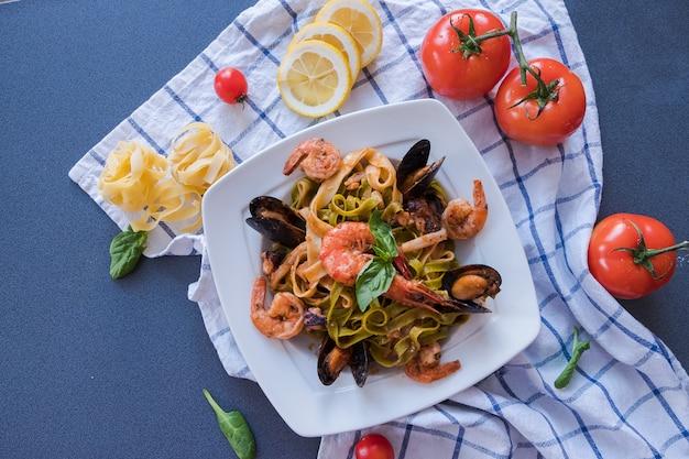Pâtes de fruits de mer aux moules et aux crevettes sur une plaque blanche. spaghetti sur fond bleu Photo Premium