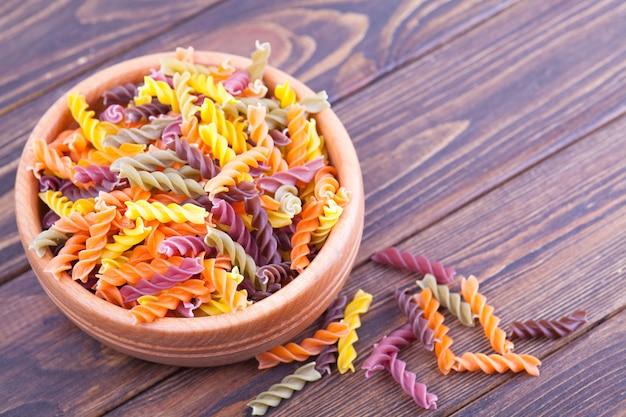 Pâtes fusilli aux épinards, carottes, betteraves dans un bol en bois sur une table sombre Photo Premium