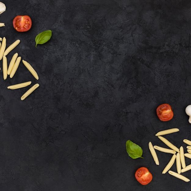 Pâtes garganelli crues aux tomates coupées en deux et au basilic au coin du fond texturé noir Photo gratuit