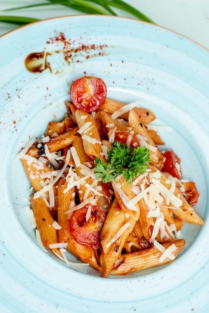 Pâtes garnies de tomates, de fromage et d'herbes Photo gratuit