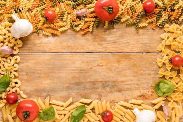 Pâtes non cuites à la tomate; feuilles d'ail et de basilic disposées sur une surface texturée Photo gratuit