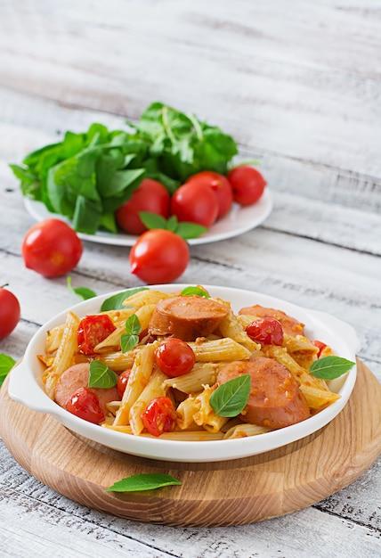 Pâtes Penne à La Sauce Tomate Avec Saucisse, Tomates, Basilic Vert Décorées Dans Une Poêle Sur Une Table En Bois Photo gratuit