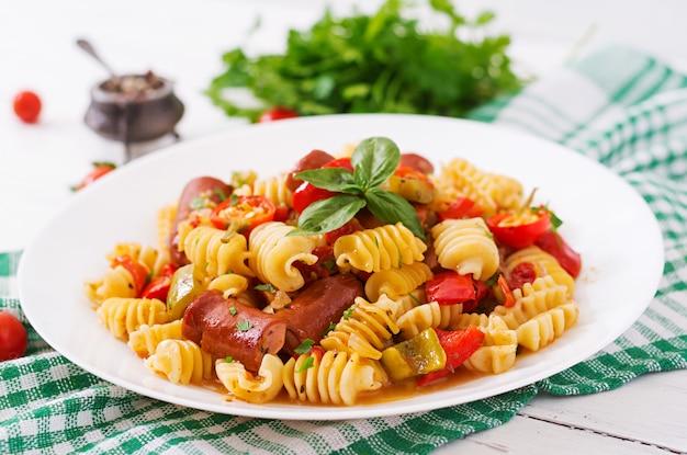 Pâtes à La Sauce Tomate Avec Saucisse, Tomates, Basilic Vert Décorées Dans Une Assiette Blanche Sur Une Table En Bois. Photo gratuit