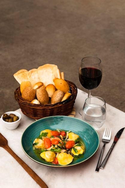 Pâtes savoureuses et panier de pain avec du vin sur la table Photo gratuit