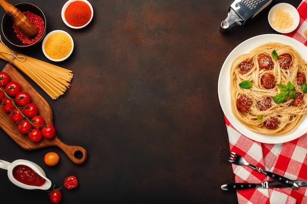 Pâtes à spaghetti aux boulettes de viande, sauce tomate cerise et fromage sur fond rouillé. Photo Premium