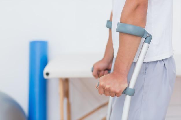 Patient debout avec une béquille dans un cabinet médical Photo Premium