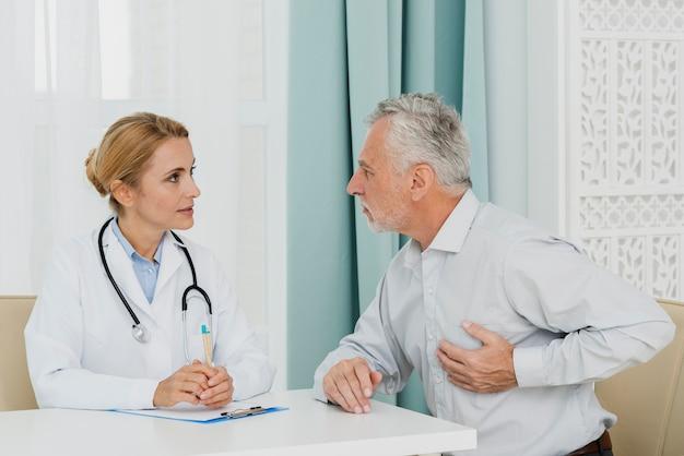 Patient localisant la douleur chez le médecin Photo gratuit