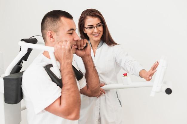 Patient masculin travaillant sur une machine médicale Photo gratuit