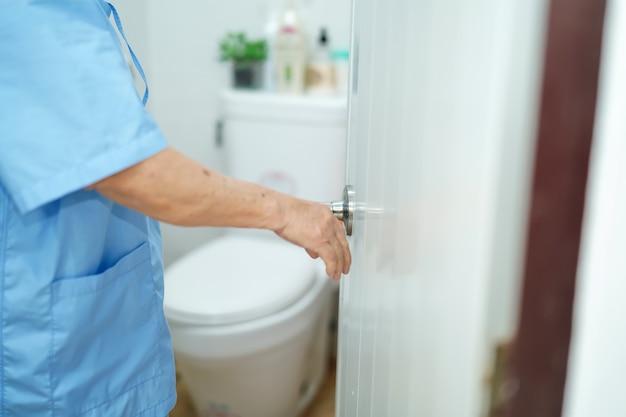Patiente âgée âgée âgée de femme âgée de femme asiatique ouvrez les toilettes à la main dans l'hôpital de soins infirmiers Photo Premium