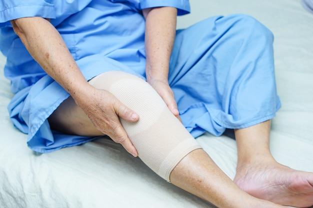 Patiente asiatique âgée ou âgée âgée avec un soutien-douleur au genou. Photo Premium