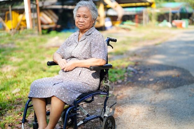 Patiente asiatique en fauteuil roulant dans le parc. Photo Premium