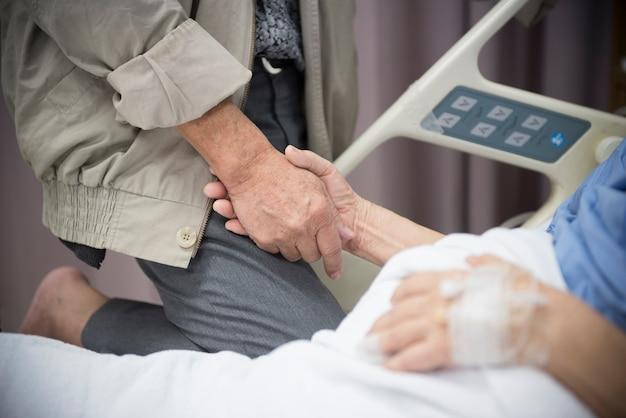 Patiente malade allongée sur un lit tenant son mari à la main à l'hôpital Photo Premium