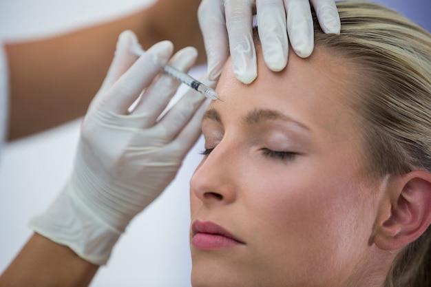 Patiente Recevant Une Injection De Botox Sur Le Front Photo gratuit