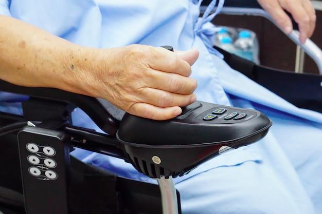 Patiente senior asiatique sur fauteuil roulant électrique. Photo Premium