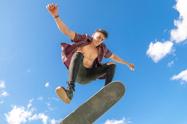 Patineur avec skateboard astuce dans skate park Photo Premium