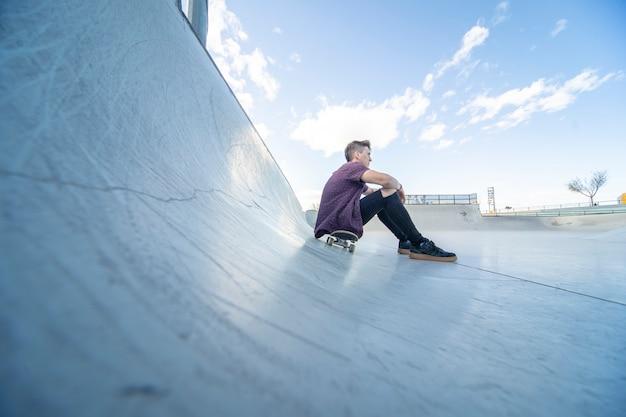 Patineur avec skateboard dans le skate park Photo Premium