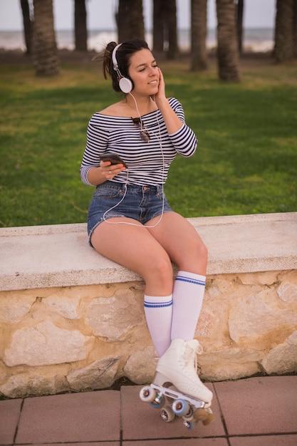 Une patineuse écoute de la musique sur un casque Photo gratuit