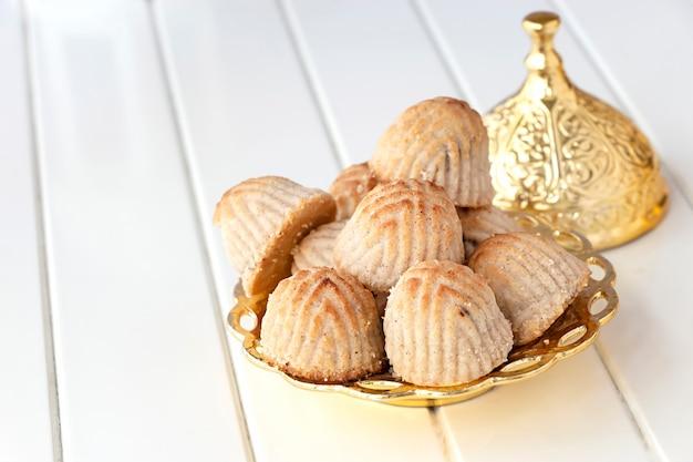 Pâtisserie Ou Biscuit Arabe Traditionnel Maamoul Aux Dattes Ou Noix De Cajou Ou Noix Ou Amande Ou Pistaches. Douceurs Orientales. Fermer. Espace En Bois Blanc. Photo Premium