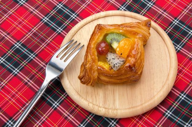 Pâtisserie danoise avec des fruits sur un plaid en tissu rouge Photo Premium