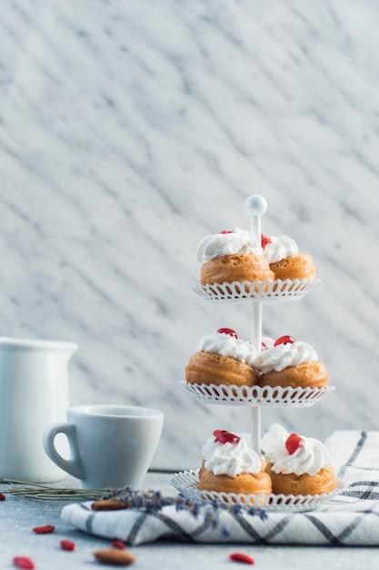 Pâtisseries fraîches sur le support de gâteau avec tasse Photo gratuit
