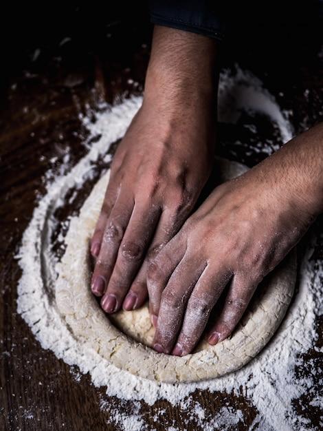 Pâtissier, main, pétrissage de la pâte crue avec de la farine blanche saupoudrée sur la table de la cuisine. Photo Premium