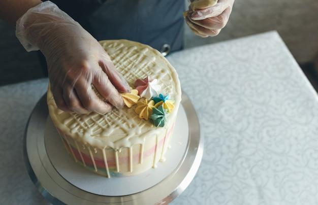 Une Pâtissière Fait Un Gâteau De Mariage De Ses Propres Mains Photo Premium