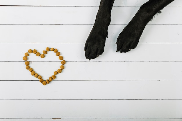 Pattes de chien près du coeur de la nourriture Photo gratuit