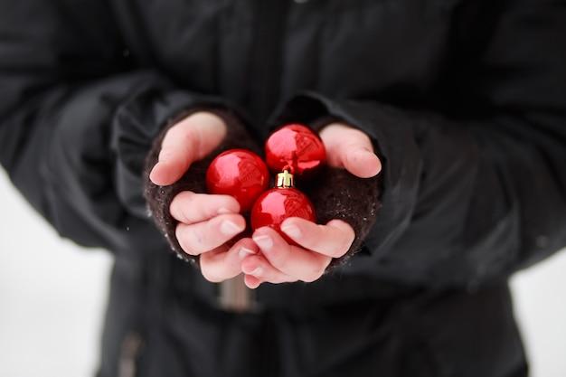 Paume Congelée D'un Enfant Debout Dans Le Froid Et Tenant Trois Boules Rouges Photo Premium