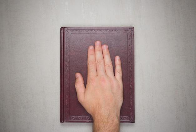 La paume d'un homme sur un livre, un serment sur la bible. Photo Premium