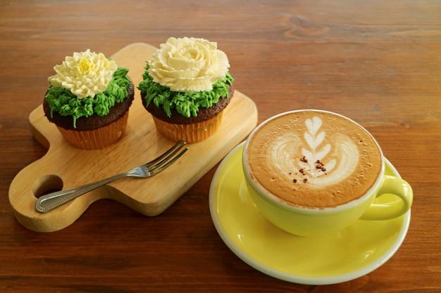 Pause café avec une tasse de cappuccino chaud et deux cupcakes garnis de crème fouettée en forme de fleur Photo Premium