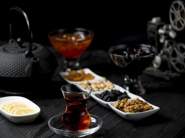 Pause thé avec un verre de thé et des collations à base de noix. Photo gratuit