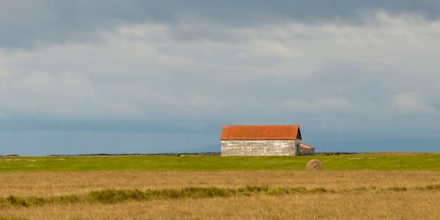 Paysage, bâtiment de ferme dans les prairies, balle de foin circulaire Photo Premium