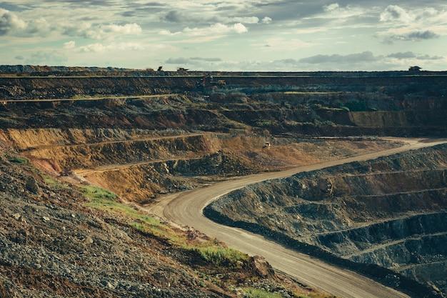 Paysage de la carrière profonde avec des machines de travail. extraction de matières premières. Photo Premium
