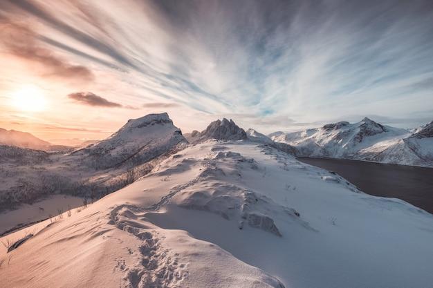 Paysage de colline enneigée colorée avec empreinte au lever du soleil Photo Premium