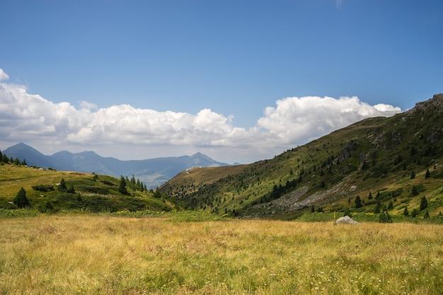 Paysage De Collines Couvertes De Verdure Avec Des Montagnes Rocheuses Sous Un Ciel Nuageux Photo gratuit