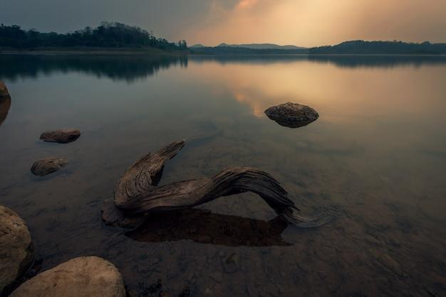 Paysage d'un coucher de soleil sur l'eau du lac avec des bois - image Photo Premium
